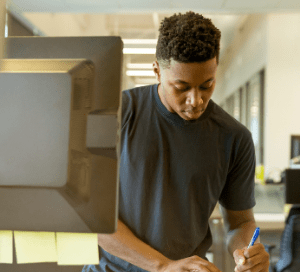 Young man writing on desk paper