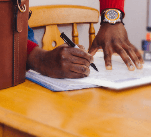 Man in red jumper signing contract